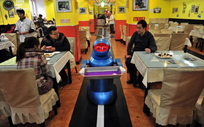 A robot that specialises in delivering food holds an empty plate after serving meals to customers at a Robot Restaurant in Harbin, Heilongjiang province January 12, 2013. Opened in June 2012, the restaurant has gained fame in using a total of 20 robots, which range in heights of 1.3 Г± 1.6 metres, to cook meals and deliver dishes. The robots can work continuously for five hours after a two-hour charge, and are able to display over 10 expressions on their faces and say basic welcoming sentences to customers, local media reported. REUTERS/Sheng Li (CHINA - Tags: SOCIETY SCIENCE TECHNOLOGY FOOD TPX IMAGES OF THE DAY)