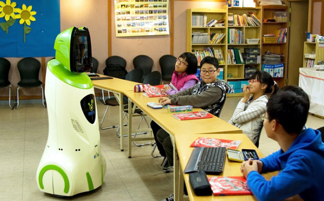 This handout photo released on March 18, 2010 by South Korea's Knowledge Economy Ministry shows an English-teaching robot (L) standing in front of children at an elementary school in Daejeon, 140km south of Seoul on December 11, 2009.  Robot teachers -- who never get angry or make sarcastic remarks -- have been a hit with pupils during a pilot project in some South Korean schools, a government report said.   RESTRICTED TO EDITORIAL USE      AFP PHOTO / HO / Knowledge Economy Ministry (Photo credit should read Knowledge Economy Ministry/AFP/Getty Images)
