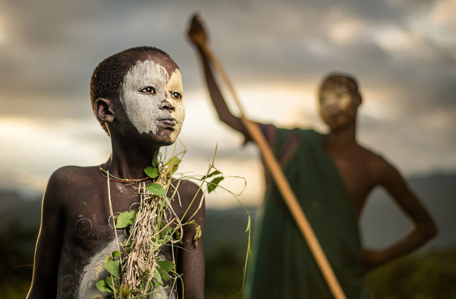 A-boy-of-the-nomadic-Suri-tribe-of-Ethiopia-in-traditional-face-body-paint-and-attire-e1436523449512