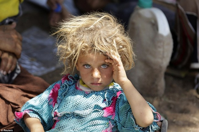 A-girl-from-the-minority-Yazidi-sect-rests-at-the-Iraqi-Syrian-border-crossing-in-Fishkhabour-Dohuk-province-after-fleeing-Isla-e1436523434434
