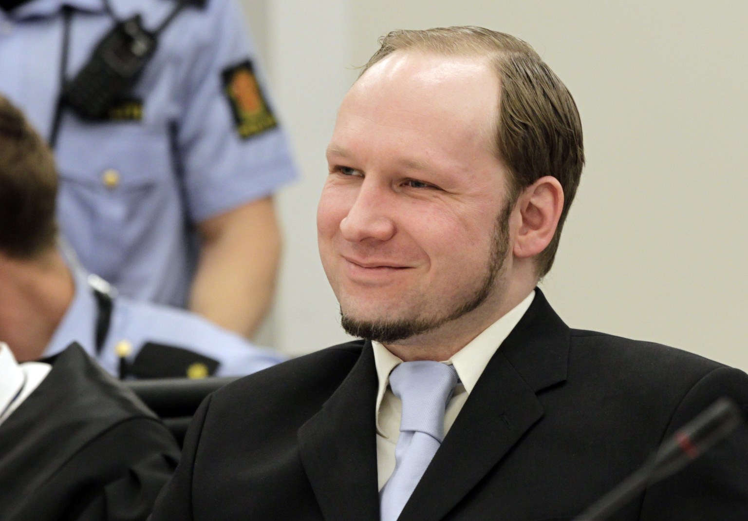 Mass killer Anders Behring Breivik smiles during his trial in room 250 of Oslo's central court on June 21, 2012.  The trial of Anders Behring Breivik, who killed 77 people in Norway last July, enters the final stretch with the prosecutors' call for him to be sent either to prison or to a psychiatric ward. Prosecutors Svein Holden and Inga Bejer Engh are to begin presenting their much-awaited closing arguments at 1000 GMT, at the end of which they will reveal whether they want the court to find Breivik responsible or not for his actions. AFP PHOTO / SCANPIX/ROALD BERIT        (Photo credit should read ROALD BERIT/AFP/GettyImages)