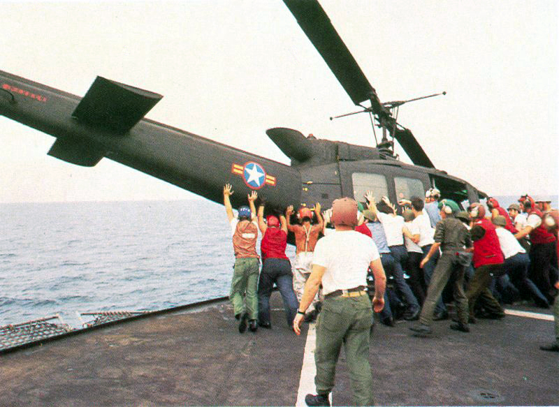 CAMP FOSTER, OKINAWA, Japan ・South Vietnamese UH-1H being pushed overboard to make room for a Cessna O-1 landing. Operation Frequent Wind, the final operation in Saigon, began April 29, 1975. During a nearly constant barrage of explosions, the Marines loaded American and Vietnamese civilians, who feared for their lives, onto helicopters that brought them to waiting aircraft carriers. The Navy vessels brought them to the Philippines and eventually to Camp Pendleton, Calif. (Official U.S. Navy photo) (released)