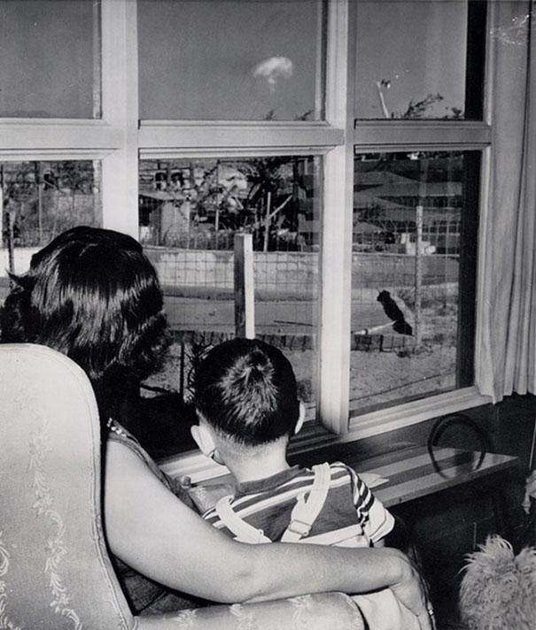 1953: A mother and son in Las Vegas look on at the mushroom cloud resulting from an atomic test