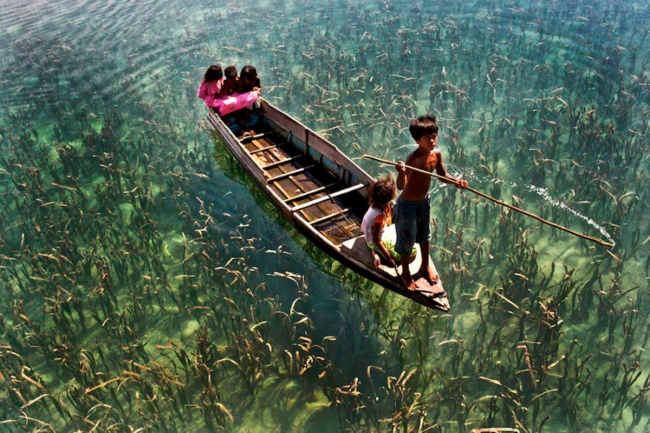Children ride on a boat on a crystal clear lake in Sabah, Malaysia.