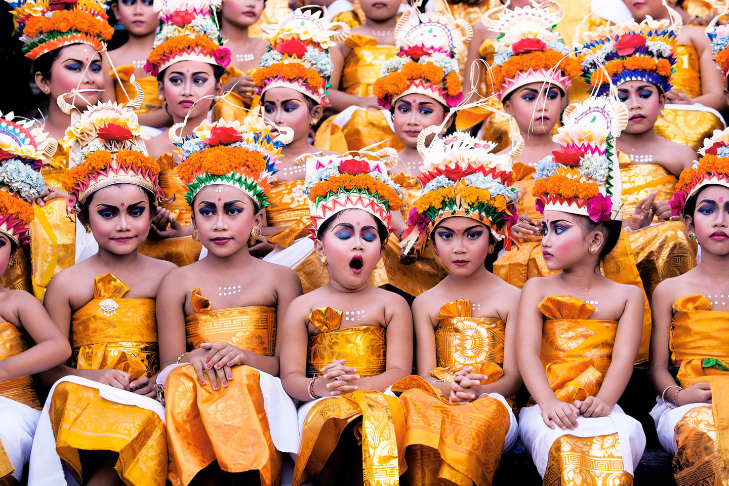 Image was taken in Bali during Melasti Festival. This Festival is conducted once a year in conjunction with Nyepi or Silent Day. These young girls were waiting for their turn to perform. They looked stunning with their bright coloured costumes and heavy make-up on, however the expression on each of the girls' face especially the yawning girl gives this image an extra 'ummpph'.