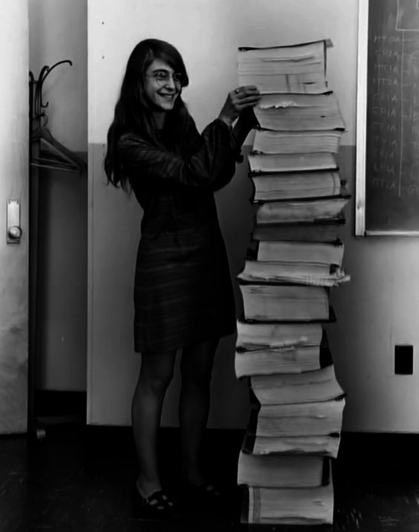 Margaret Hamilton, lead software engineer of the Apollo Project, stands next to the code she wrote by hand and that was used to take humanity to the moon. [1969