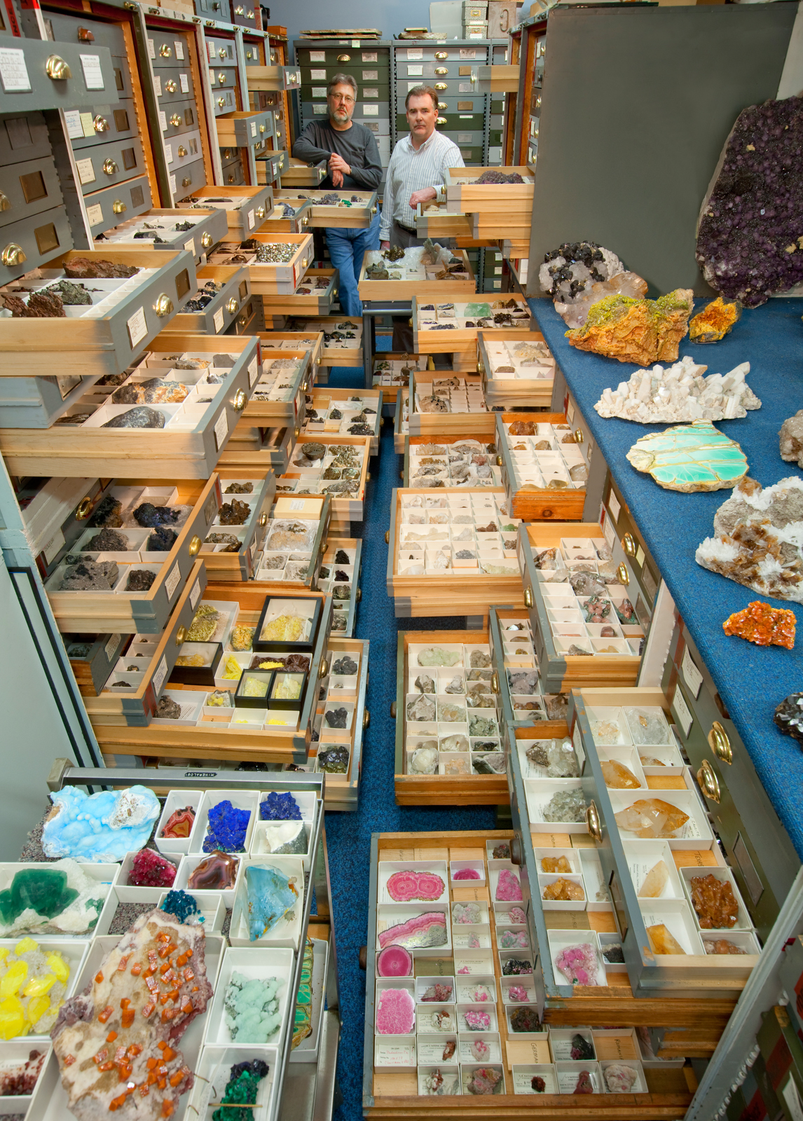 "An assortment of mineral specimens from the Department of Mineral Sciences' collections are displayed in the storage vault known as the ""Blue Room,"" at the Smithsonian Institution's National Museum of Natural History. Mineral Sciences staff present are (left) Paul Pohwat, Collections Manager of Minerals, and (right) Russell Feather, Collections Manager of Gems."