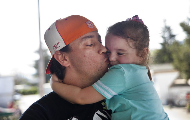 Bryan Thouvenel gives his daughter Harmony, 5, a kiss while standing for a portrait in front of their home in Myrtle Creek, Saturday, April 3, 2016.