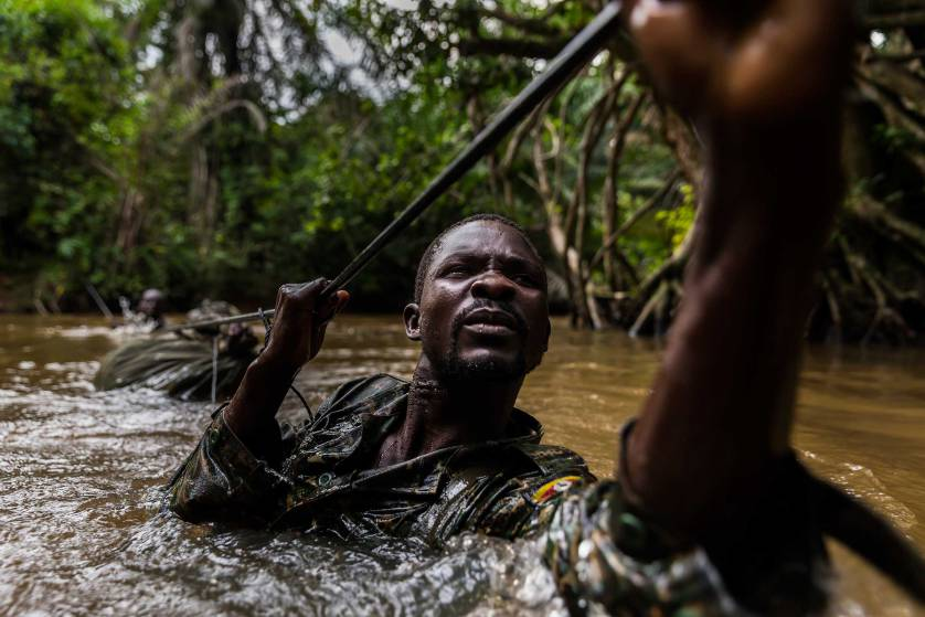 MBOKI, CENTRAL AFRICAN REPUBLIC, 25 NOVEMBER 2014: Ugandan soldiers cross one of many rivers while on patrol against the Lord's Resistance Army close to the border of the DRC. The Ugandan contingent based in CAR are focused on the aprehension of the Lord's Resistance Army, LRA, the notorious rebel group led by Joseph Kony which has terrorized citizens of Uganda, C.A.R, South Sudan and the Democratic Republic of Congo for the last 4 decades. Soldiers are seen crossing a river, a technique they have perfected with ropes despite the fact that many of the men cannot swim. The LRA contingent they are hunting is coming from Garamba National Park where they have been hunting ivory, a task ordered by Joseph Kony and detailed in a commander's diary that this Ugandan contingent captured in an ambush earlier in 2014. Defectors say that Joseph Kony, leader of the LRA, is increasingly reliant on ivory as a means of trade for weapons and supplies from their hosts the Sudanese Army.