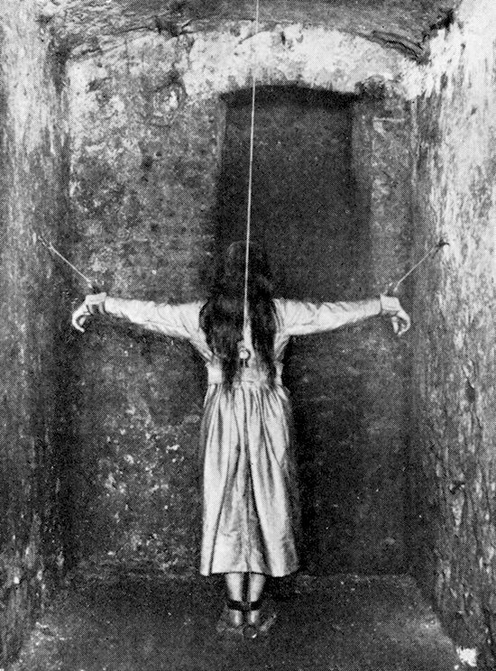A woman being hanged by her wrists and neck in a Victorian insane asylum.