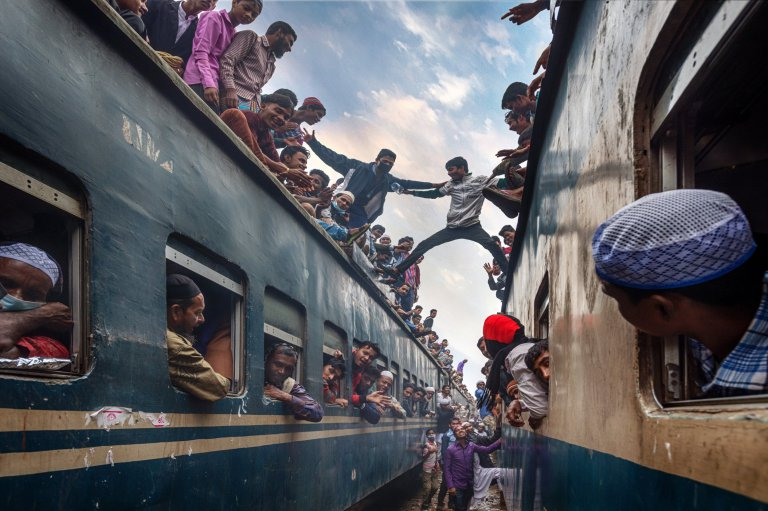 The youngster are having fun at the roof top of the train. There are too many people who rushing home after the Bishwa Ijtema at Tongi train station of Bangladesh.