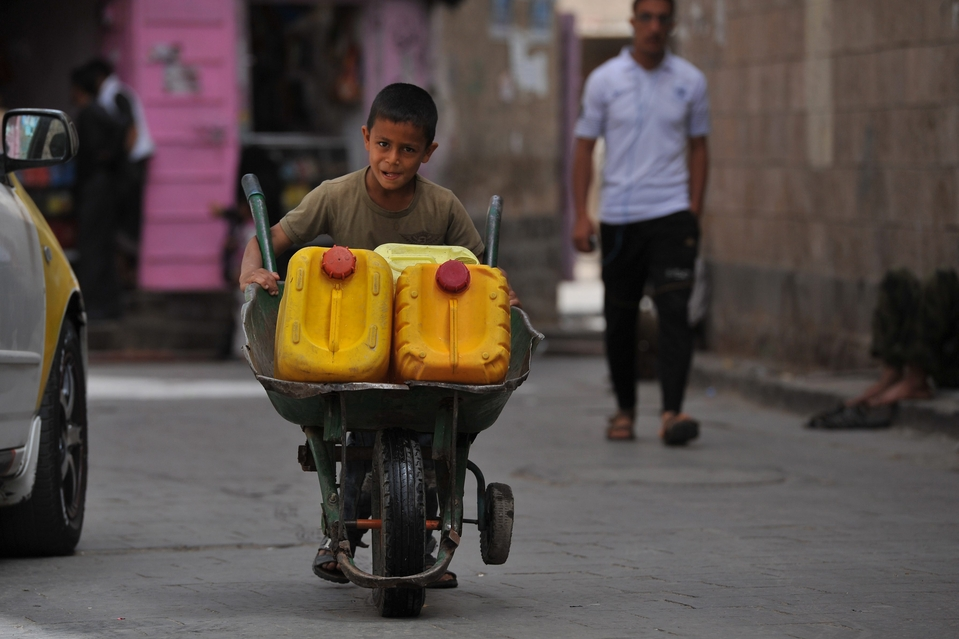 "epa03741555 A Yemeni boy pushes a wheelbarrow with containers full of water inside, after he collected them from a public tap in the old city of Sana'a, Yemen, 12 June 2013. World Day Against Child Labor is celebrated around the world every 12 June to raise awareness and contribute to ending child labor. The theme of this year's ""No to child labor in domestic work"". EPA/YAHYA ARHAB"