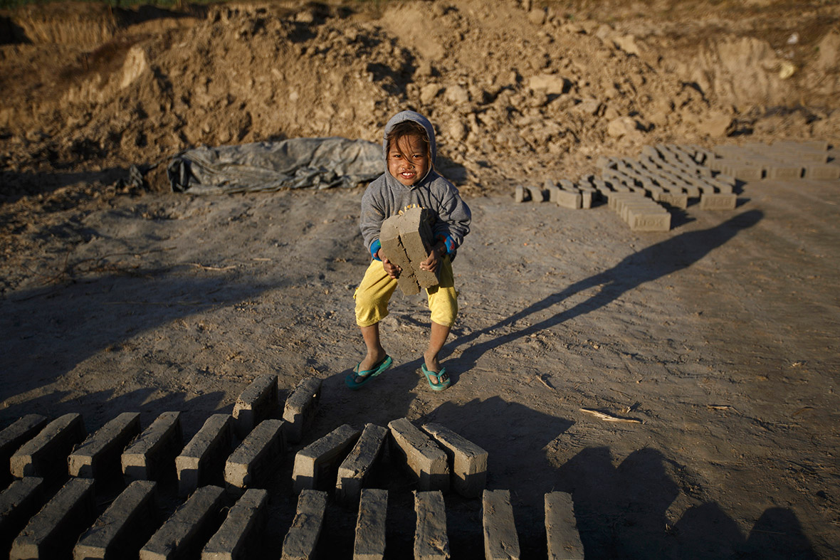 An Afghan child labourer arranges bricks at a factory in the outskirts of Herat