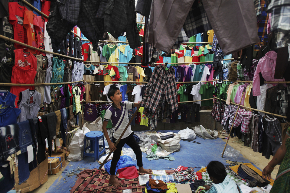 An Indian boy displays readymade garments for sale in New Delhi, India, Wednesday, June 12, 2013. The International Labor Organization (ILO) observes June 12 as the World Day Against Child Labor to highlight the plight of child laborers. (AP Photo/Altaf Qadri)