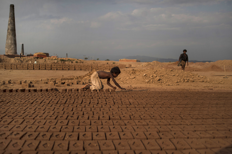 Pakistani child, Jabro Mounir, 6, arranges bricks during his daily work in a brick factory, on World Day Against Child Labor, on the outskirts of Islamabad, Pakistan, Wednesday, June 12, 2013. The World Day Against Child Labor is observed on June 12 across the world including Pakistan to raise awareness and contribute to end child labor. Jabro earns 200 Rupees ($2.030 cents) per day. (AP Photo/Muhammed Muheisen)