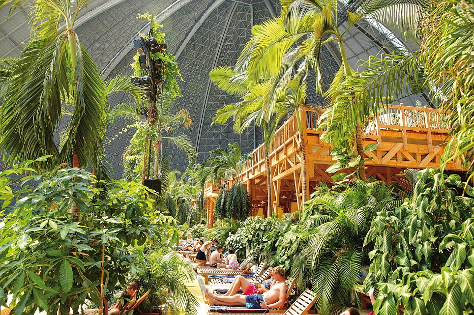 hese are the incredible images of a tropical island paradise INSIDE a building so big could easily fit eight football pitches. A sandy beach, spa, waterfall, whirlpools and water slides are just a few of the attractions inside the old airship hanger. The indoor tropical island, located in Brandenburg, Germany, boasts an air temperature of 26 degrees, with water being 28C in the Tropical Sea and 32 C in the Bali Lagoon. Inside the paradise also host to the worlds biggest indoor rainforest, which features over 50,000 plants and spans over a 10,000 metre square area