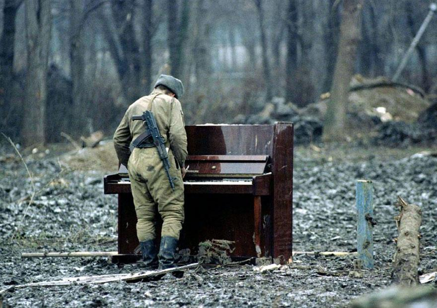 Russian soldier playing an abandoned piano in Chechnya in 1994