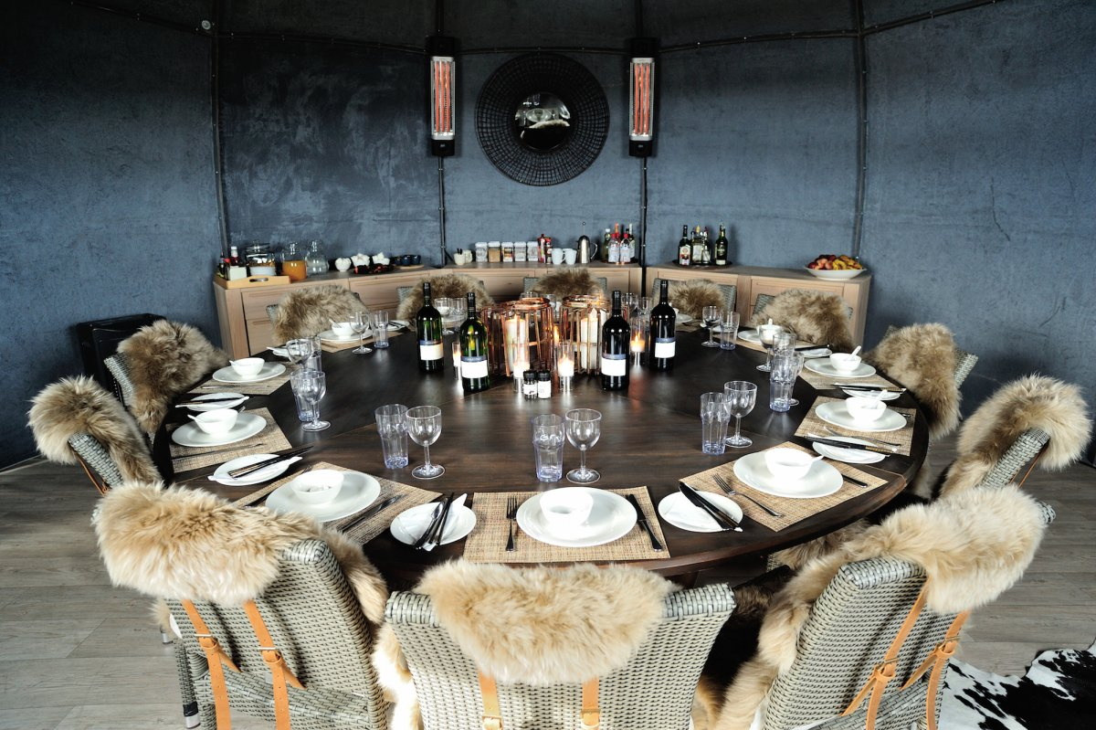 in-the-dining-room-an-oak-table-surrounded-by-fur-chairs-makes-for-a-rustic-setting