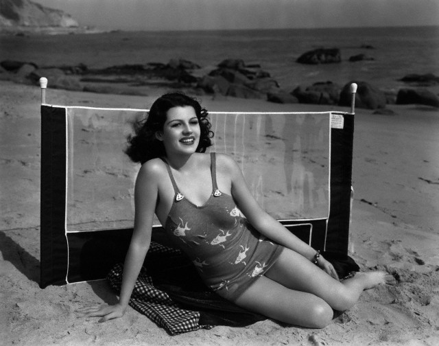 1937 --- Original caption: 1937- Sunny Days Are Here Again: and Columbia's Rita Hawyworth leads the beachward trek. The dark-eyed, dark-haired starlet dons her favorite flying-fish swimming suit, sets up her wind break, and she is ready for a lazy day at the seashore. Miss Hayworth is currently making a comedy-drama about a girls' professional softball team, which Lambert Hillyer will direct, with Charles Quigley as leading man. --- Image by © Bettmann/CORBIS